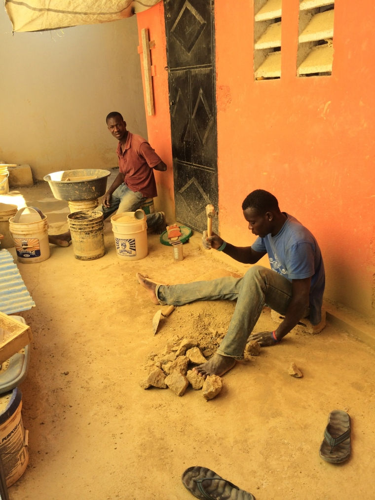 Workers at the Papillon factory pound rocks into dust for clay beads.